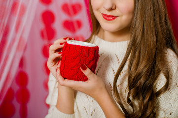 Beautiful girl with a cup of tea on a pink background