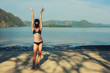 Woman wearing bikini and balaclava on beach