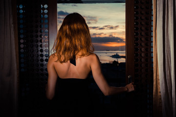 Sexy woman looking out french doors at sunset
