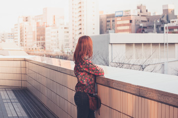 Woman looking at skyline at sunset