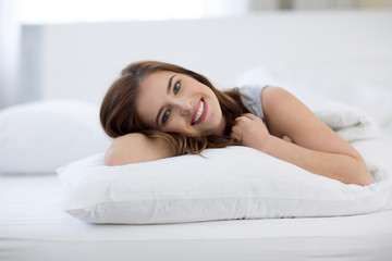 Young beautiful smiling woman lying on the bed at home