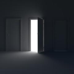 Dark room with the door open and the light behind her.
