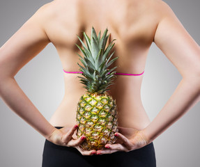 Unrecognizable fit woman with pineapple