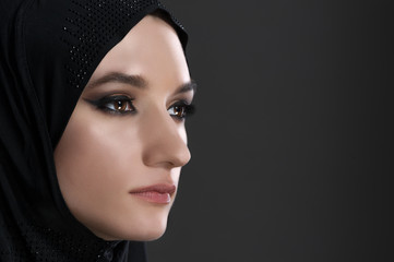 pretty young muslim woman head shot over gray background