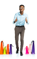 Happy african american man with fingers up and shopping bags on