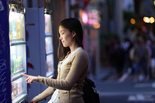 Japan vending machines - Tokyo woman buying drinks