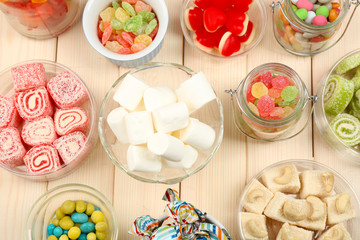 Sweetness in different containers on wooden background