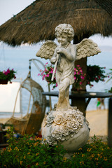 Sculpture of angel stand on quay with sea view