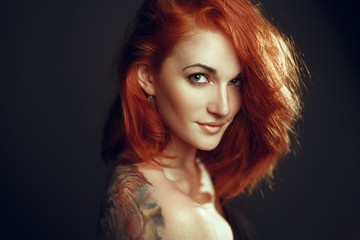 girl with red hair and with tattoo on shoulder