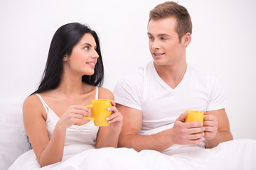 Couple in bed drinking tea or coffee