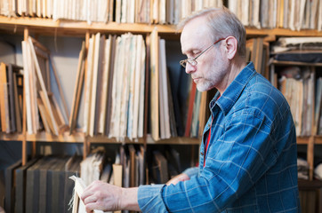 An artist in glasses preparing canvas