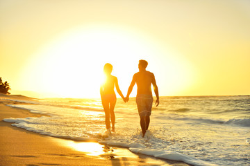 Romantic honeymoon couple in love at beach sunset
