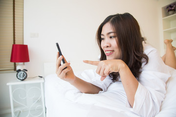 Young happy asian woman using smartphone