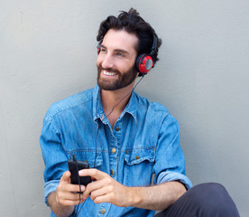 Happy man sitting with headphones and mobile phone