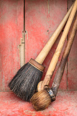Old paint brushes against a red wooden background