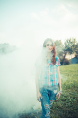 beautiful young hipster woman smoke fog in the park