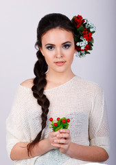 portrait of a beautiful brunette with red flowers in her hair