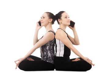 Two Yogi female talking on the mobile phone in yoga Lotus Pose