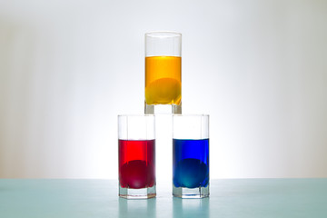 three glasses with colored liquid and eggs inside