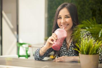 Hispanic girl drinking a smoothie