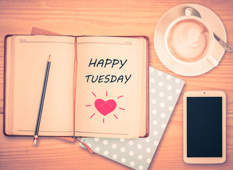 Happy Tuesday on notebook , pencil, smart phone and coffee cup w