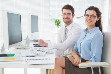 Smiling team sitting at desk