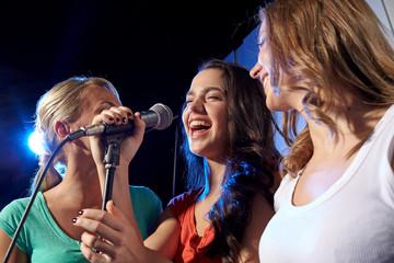 happy young women singing karaoke in night club Fotobehang