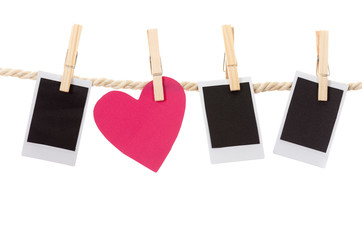instant photographs and heart shape hanging on a rope