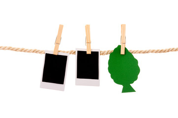 instant photographs and tree shape hanging on a rope clothesline