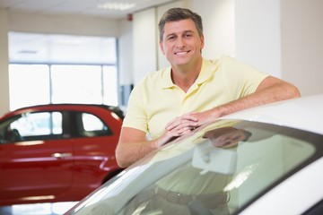 Smiling customer leaning on car