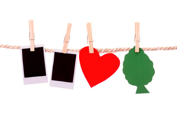instant photographs and tree heart shapes hanging on a rope