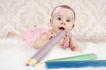 Little baby girl lying on the floor with big crayons