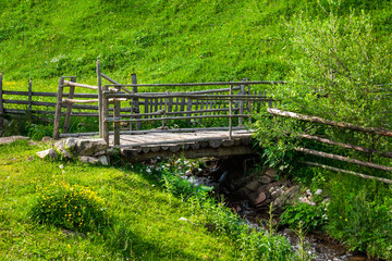 wooden bridge over narrow stream