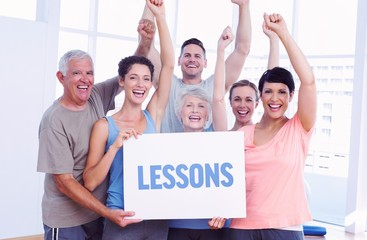 Lessons against portrait of happy fit people holding blank board