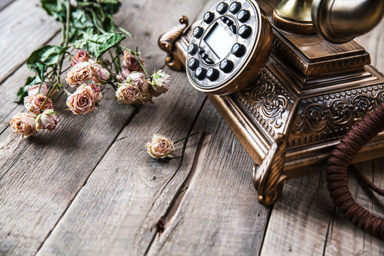 Old vintage black rotary phone and a bouquet of roses