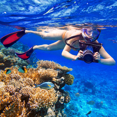 Young women snorkeling in the tropical water with camera