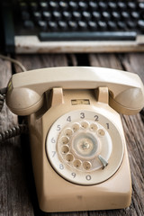 Retro rotary telephone  and typing machine on wooden background.