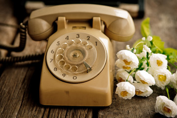 Old vintage telephone with flower on wooden table.