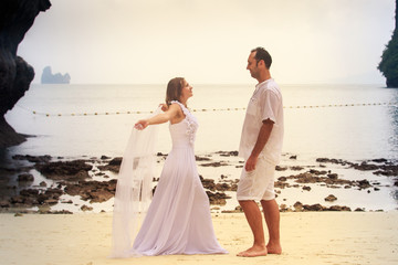 bride and groom dance barefoot on sand beach