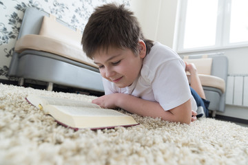 Boy reading a book while lying on  carpet in the room