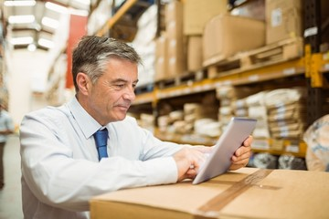 Warehouse manager working on tablet pc