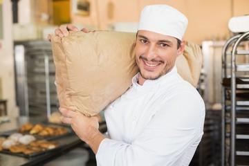 Smiling baker holding bag of flour