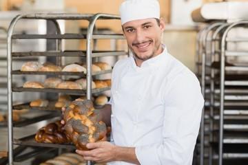 Smiling baker holding fresh loaf