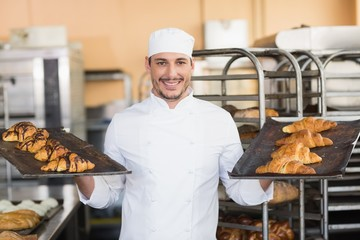 Smiling baker holding trays of croissants