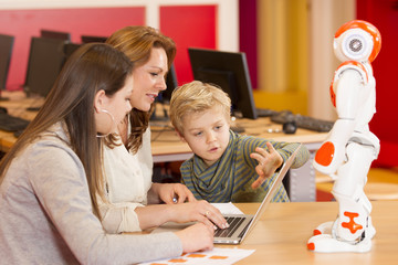 Female teacher programming robot with children
