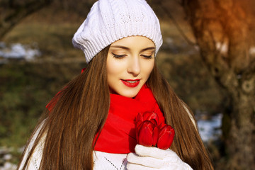 Spring portrait of a girl with red tulips