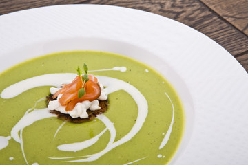 Bowl of healthy green pea soup topped with cream and fresh