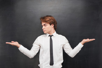 Man with palms up making a choice on chalkboard background