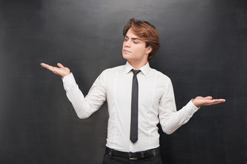Young man with one palm above on chalkboard background