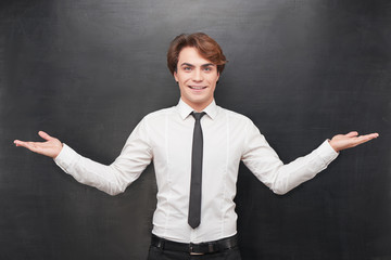 Cheerful man with palms up on chalkboard background